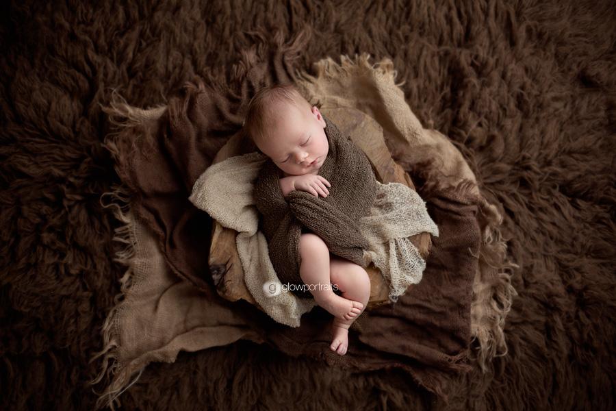 newborn boy wrapped lying on fur