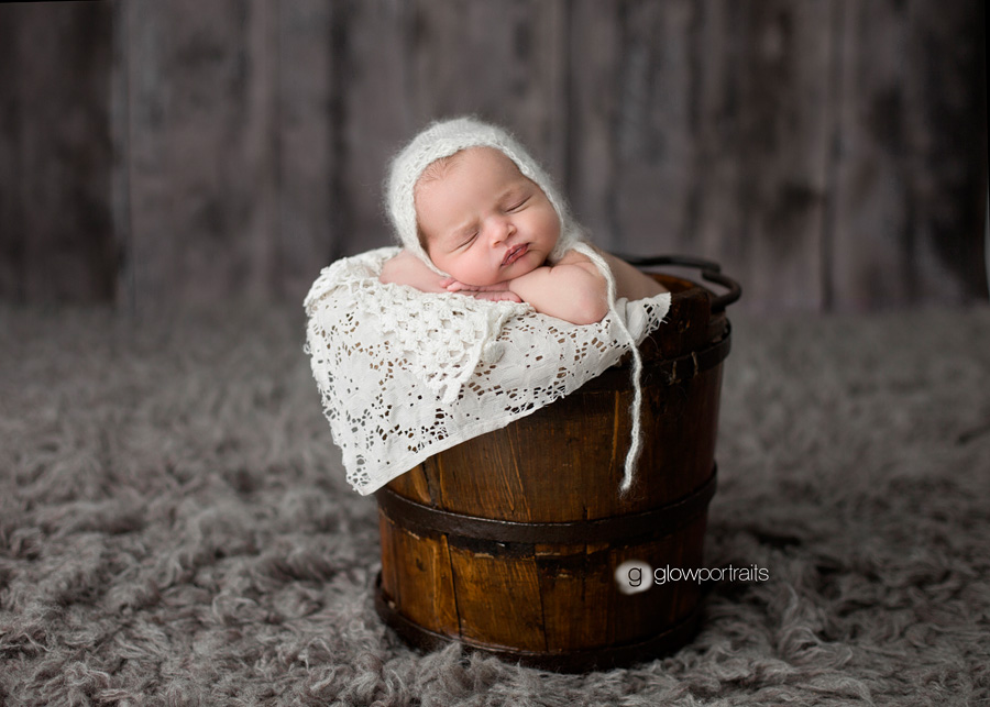 baby in bucket with bonnet