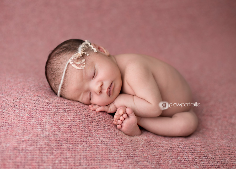 Newborn baby girl on fur beanbag taco pose