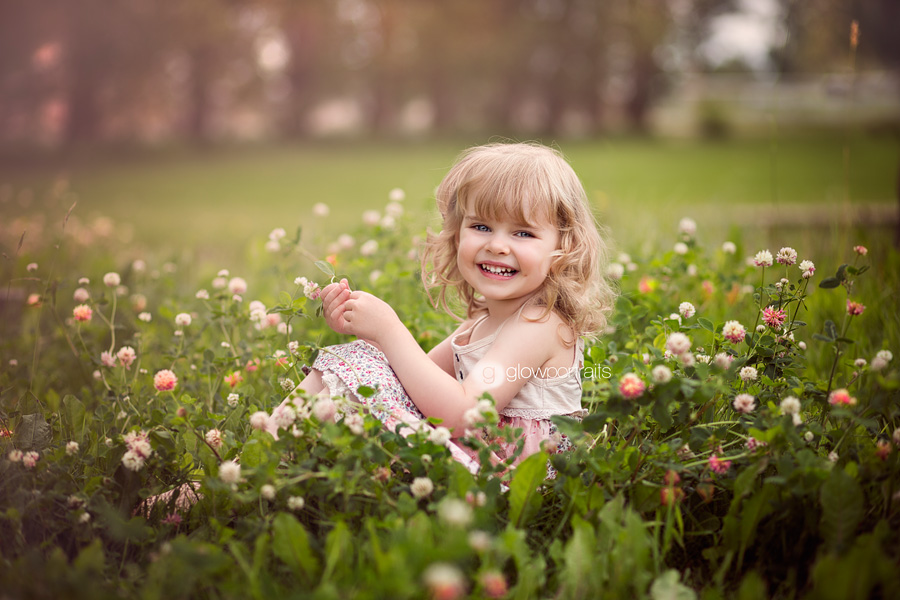 little girl sitting in flower field