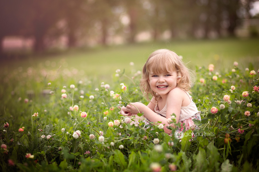 girl sitting in flower field smiling