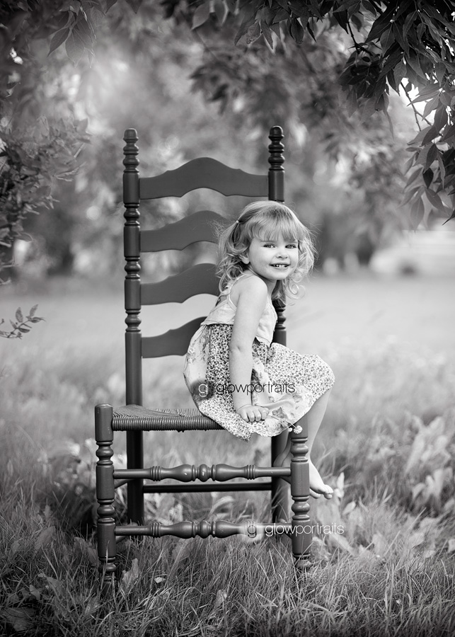 litte girl sitting on chair outdoors black and white image
