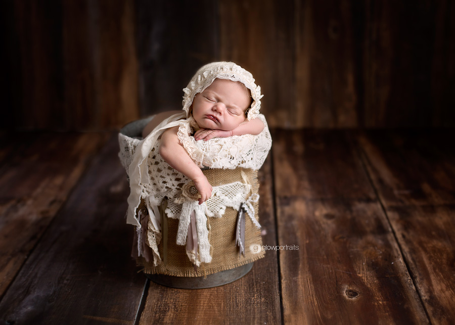 baby girl in bucket with lace bonnet