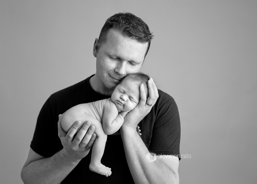dad snuggling newborn