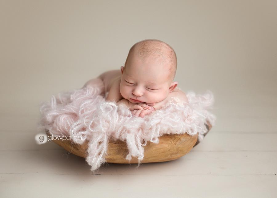 newborn baby girl in pink fluff in wooden bowl