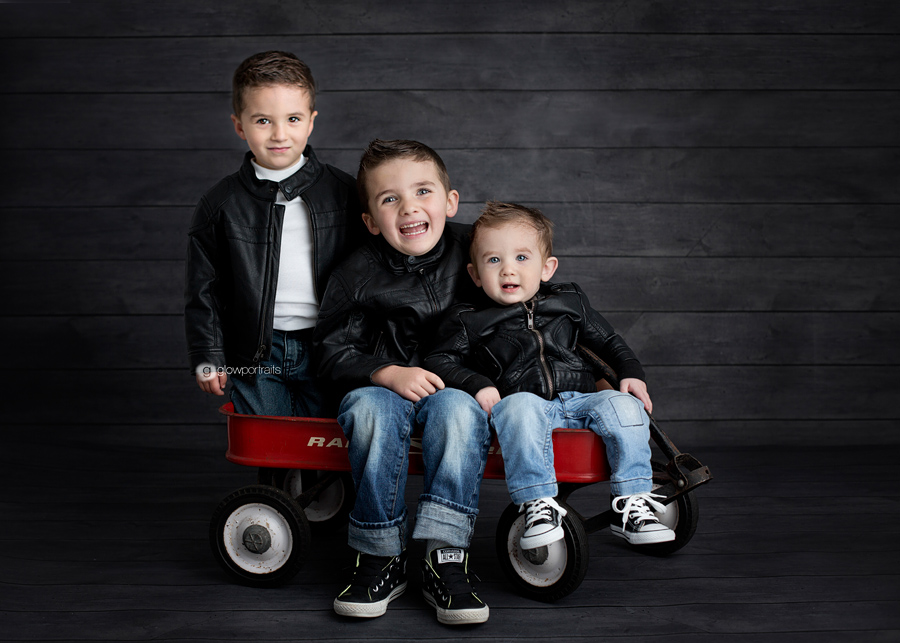 three boys wearing black leather jackets sitting on red wagon
