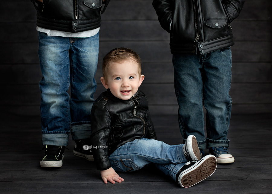 baby boy wearing leather jacket sitting by brothers feet