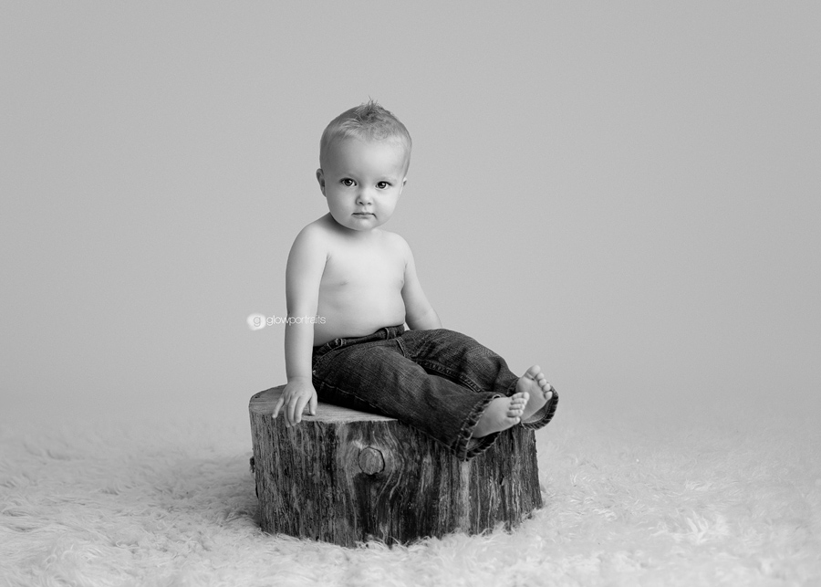 baby sitting on wooden stump