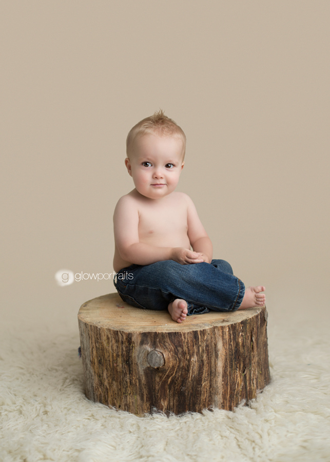 baby boy sitting on stump with jeans on