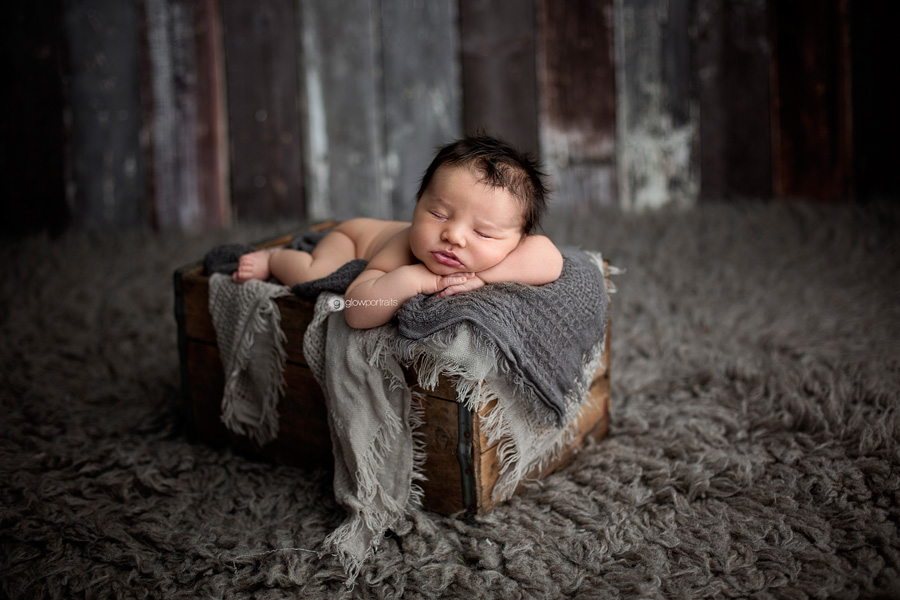 newborn baby in box with blankets on fur rug