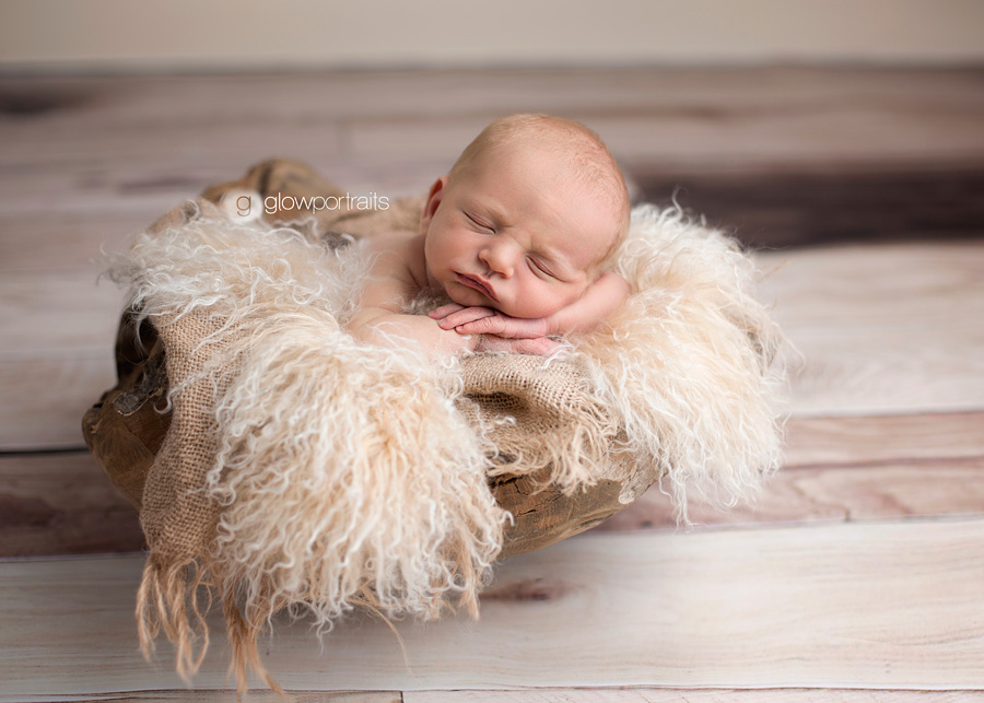 newborn in wooden bowl with fur