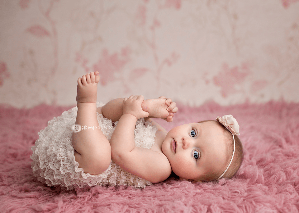 baby wearing lace romper grabbing toes