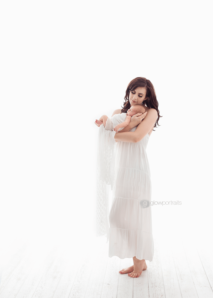 mom snuggling baby wearing white dress