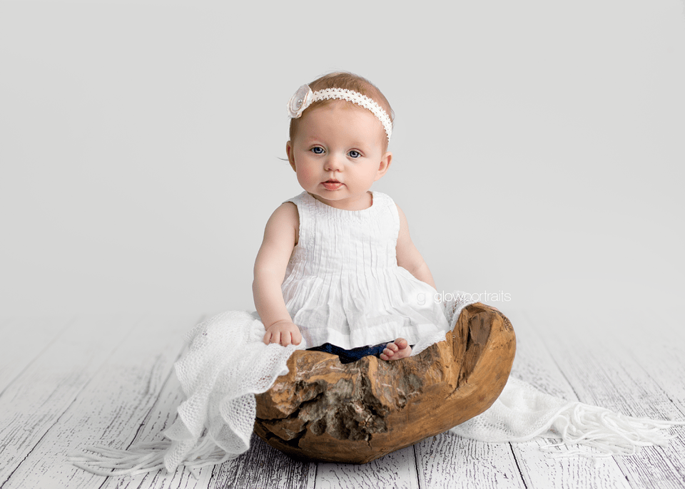 baby girl wearing white dress sitting in wooden bowl