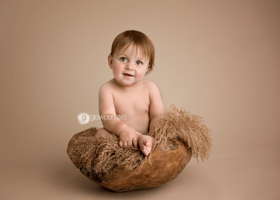 cute little boy baby sitting in wooden bowl